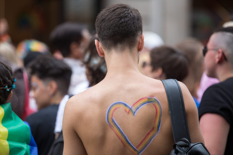 Colour image depicting a young man in a crowd at the Pride in London Parade on Saturday July 6th, 2019 on Regent Street - which is in the city centre of London, UK   The young man has a large rainbow coloured heart painted on his back. The rainbow colours are a symbol of the LGBTQ community. Regent Street is filled with people who are wearing colourful outfits, face and body paint, and the rainbow flag is prevalent.  The young man has his back towards the camera, in the direction of the parade and appears to have his head slightly faced downwards.  Pride in London is an annual LGBT pride festival and parade held each summer in London, the Capital of the United Kingdom.